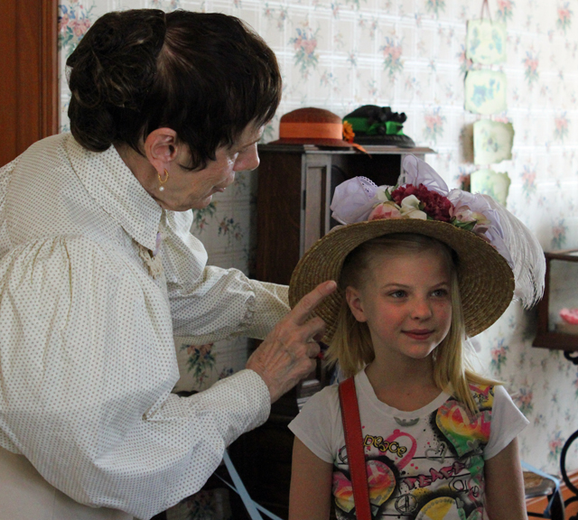The presenter adjusts a visitor's hat