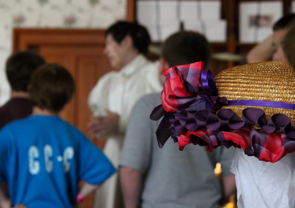 The presenter tells some visitors about the shop - Mrs. Cohen's Millinery, Greenfield Village
