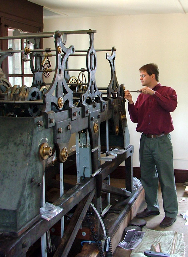 Man using a screwdriver on a large and elaborate piece of machinery