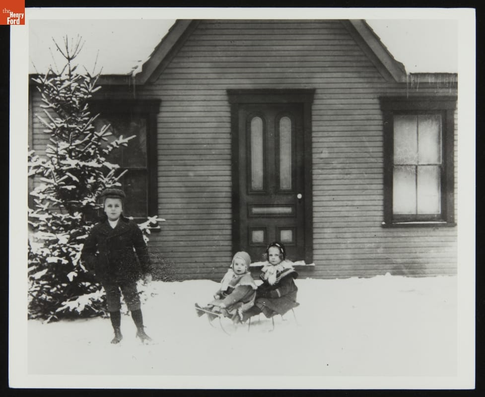 Two children sit on a sleigh in snow in front of a door; another boy stands nearby in front of a tree