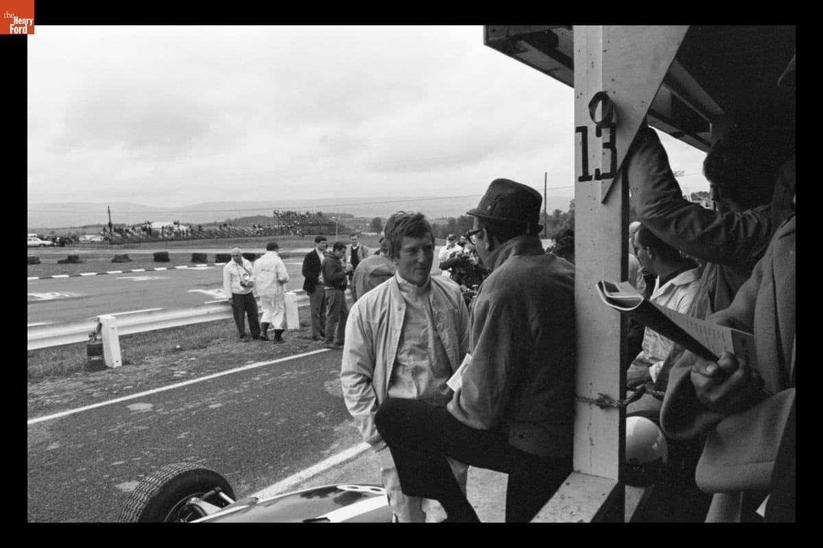 Two men talking; other people in foreground to right and in background are more people and a raceway