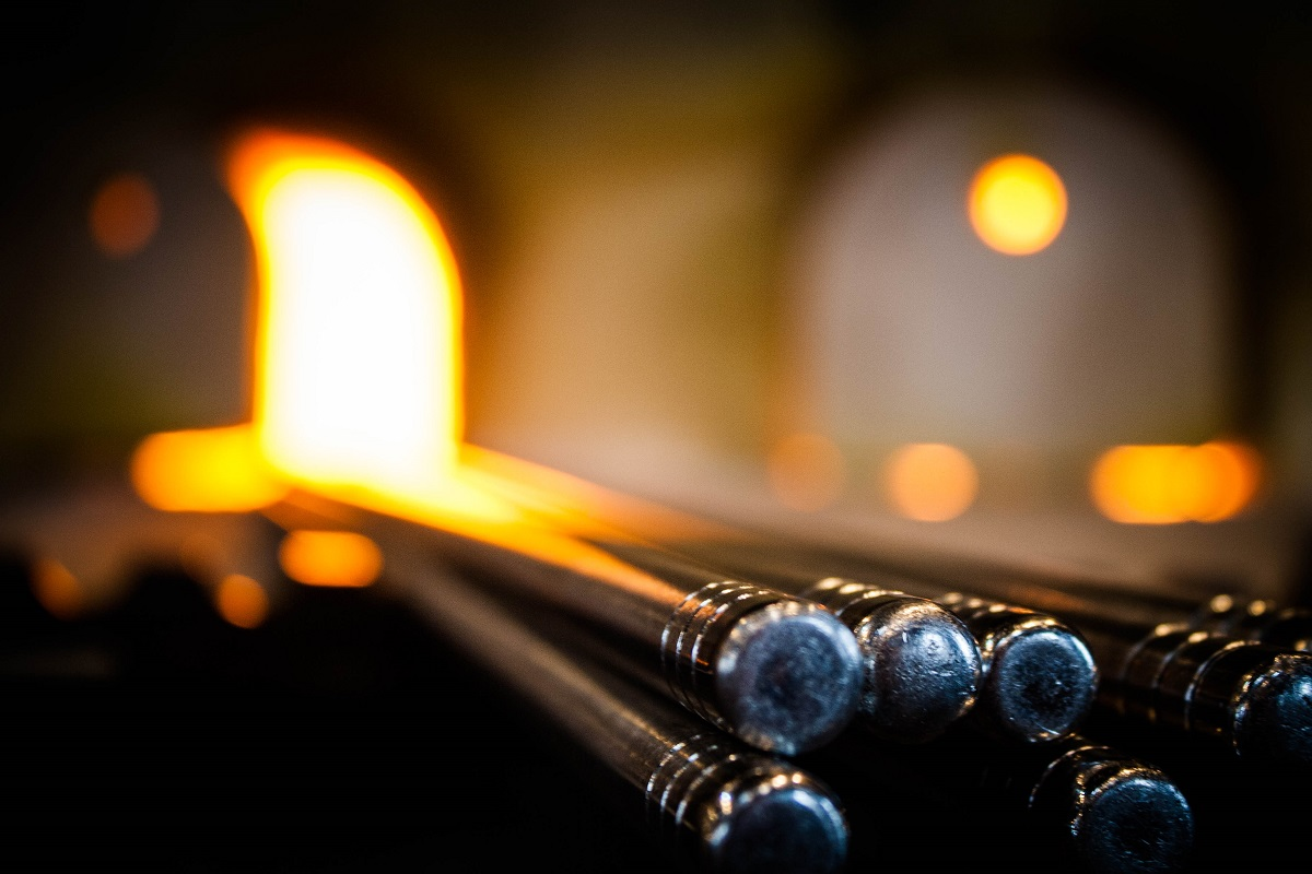 Metal rods with flame visible in the out-of-focus background
