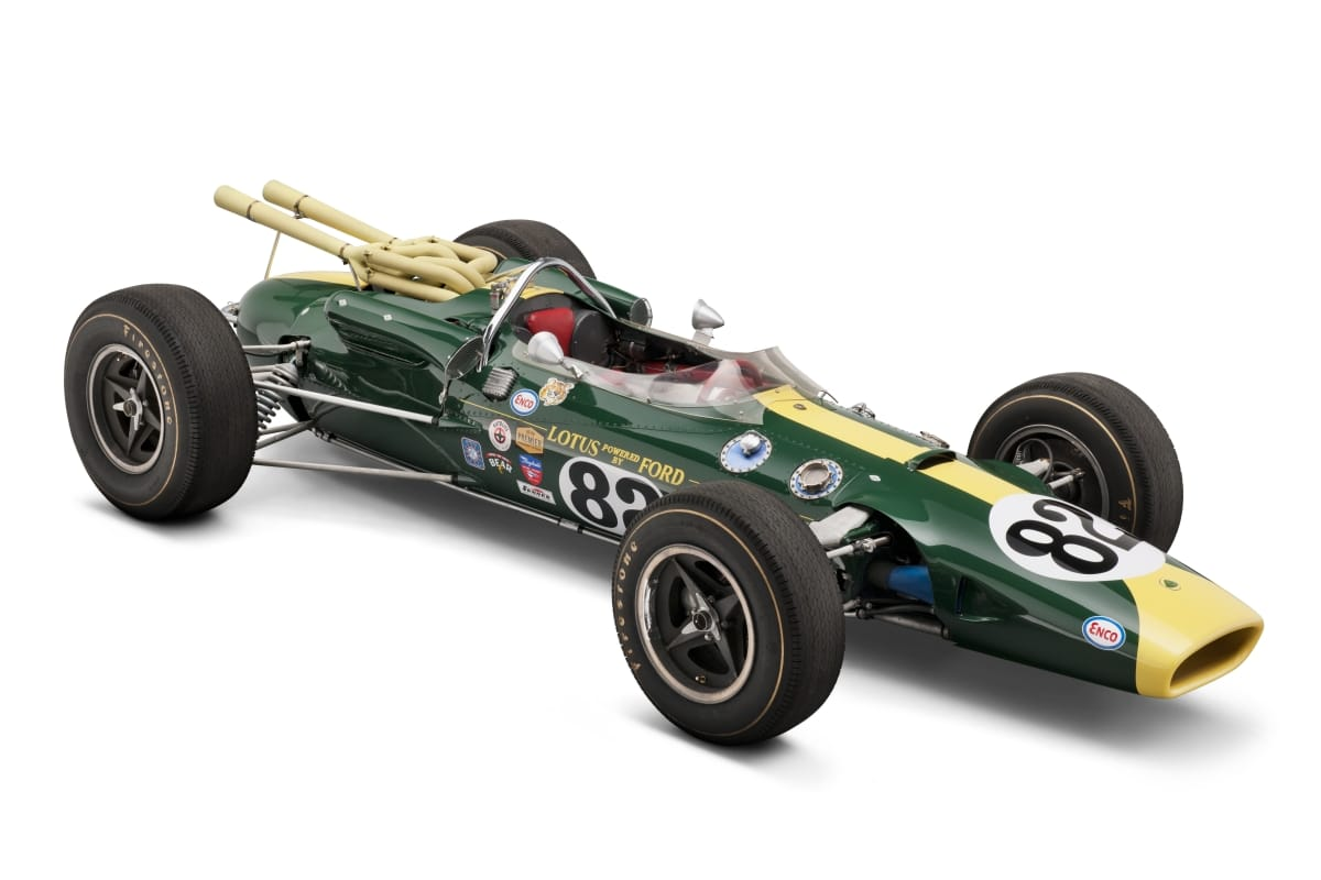 Long, low, torpedo-shaped green and yellow race car with large tires and open cockpit