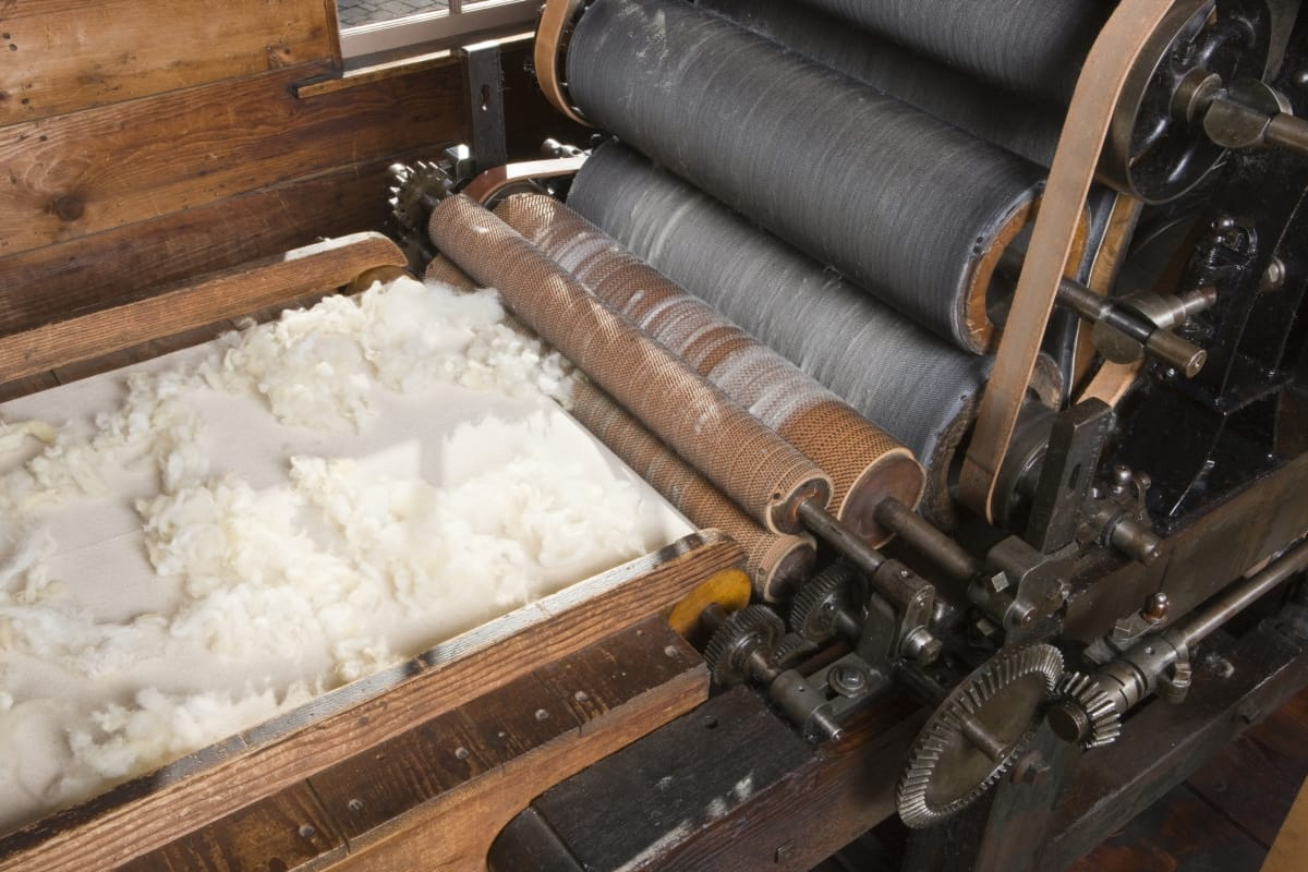 Conveyor belt with wool on it, headed for a machine with a series of large rollers