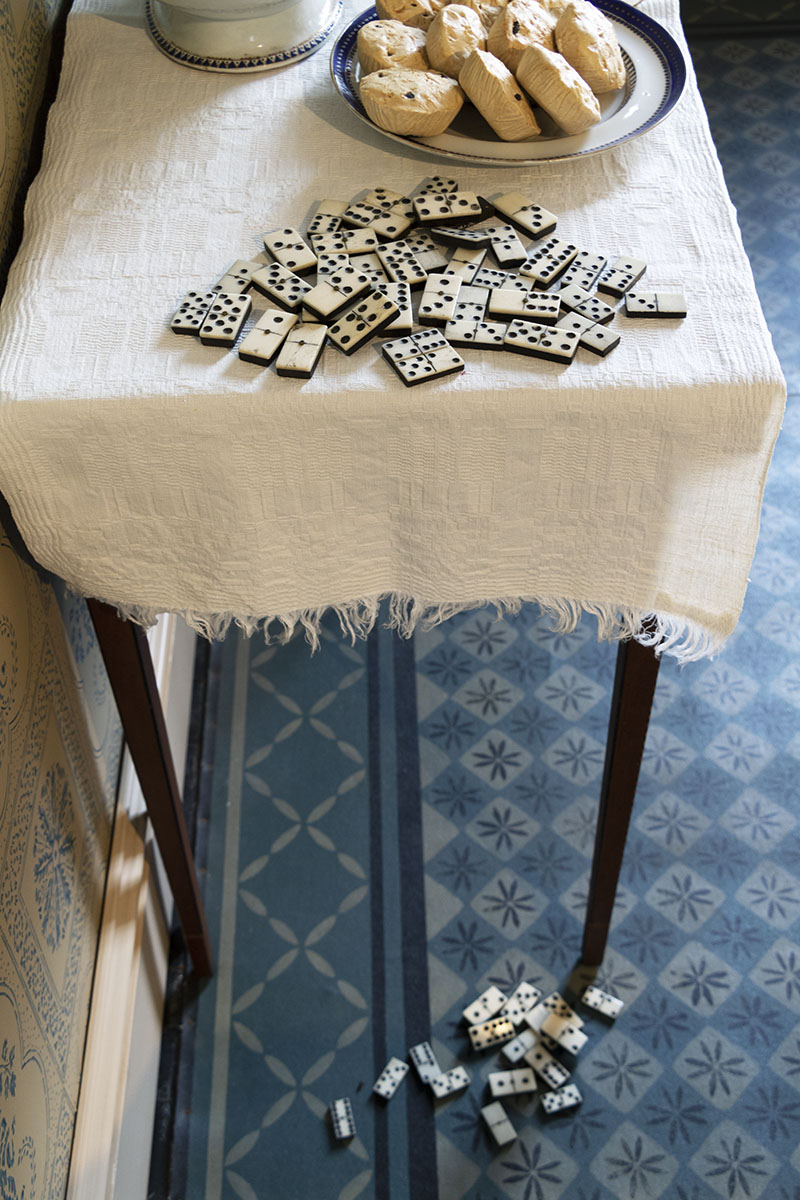 End of table covered with cloth with dominos and plate of scones on it; additional dominos on patterned floor below
