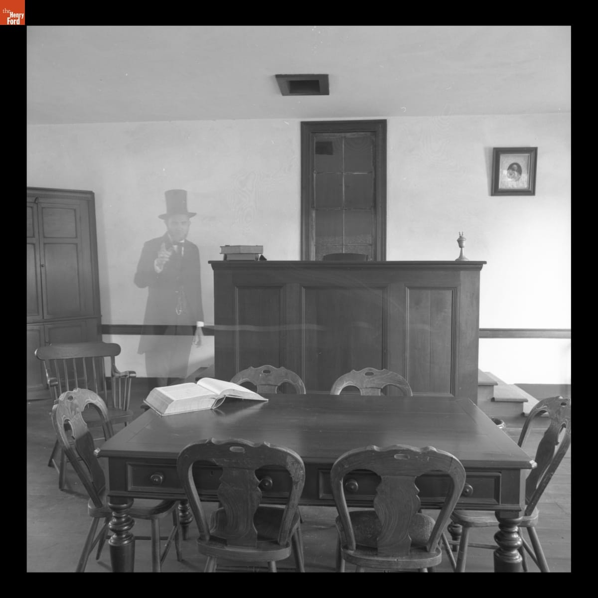 Transparent figure of Abraham Lincoln standing in room with table and dais
