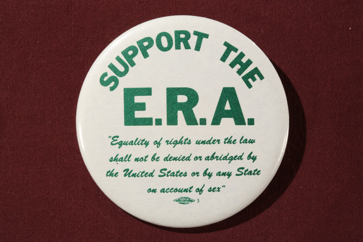 "Round white button with green block text reading in part ""Support the E.R.A."""