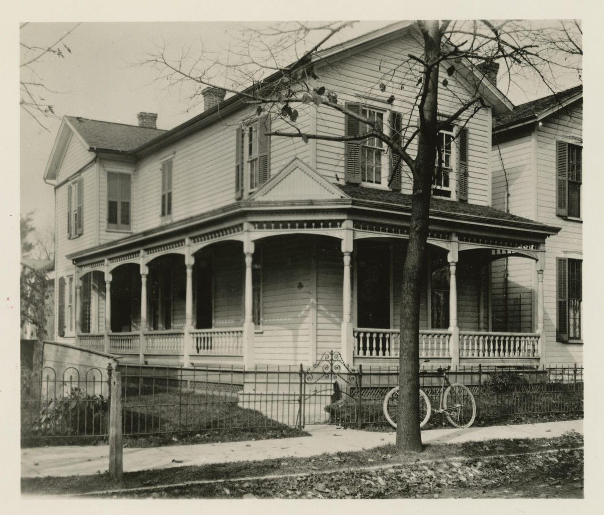 Outside view of two-story house with wrap-around porch and bicycle propped against fence