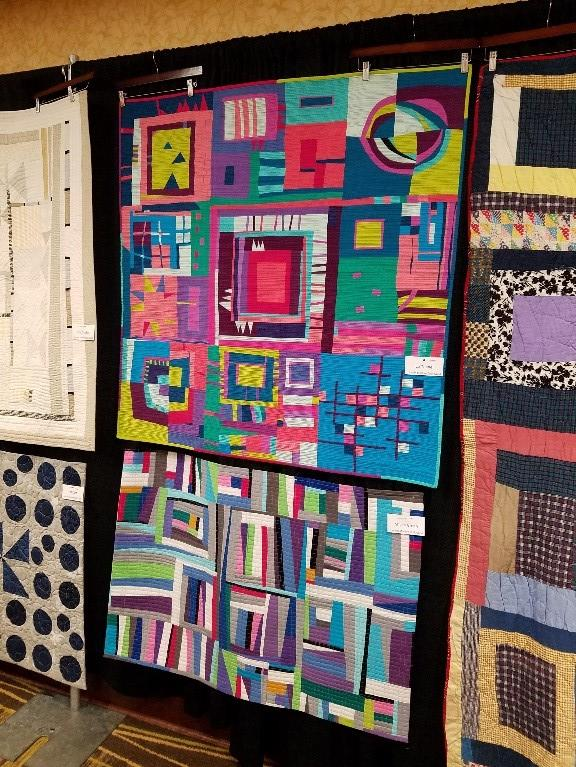 Brightly colored quilts hanging on a black backboard