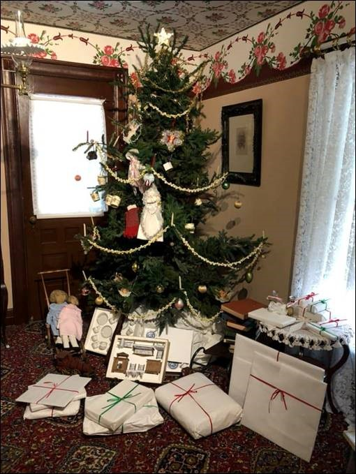 Decorated Christmas tree in corner of room with wrapped and unwrapped items underneath