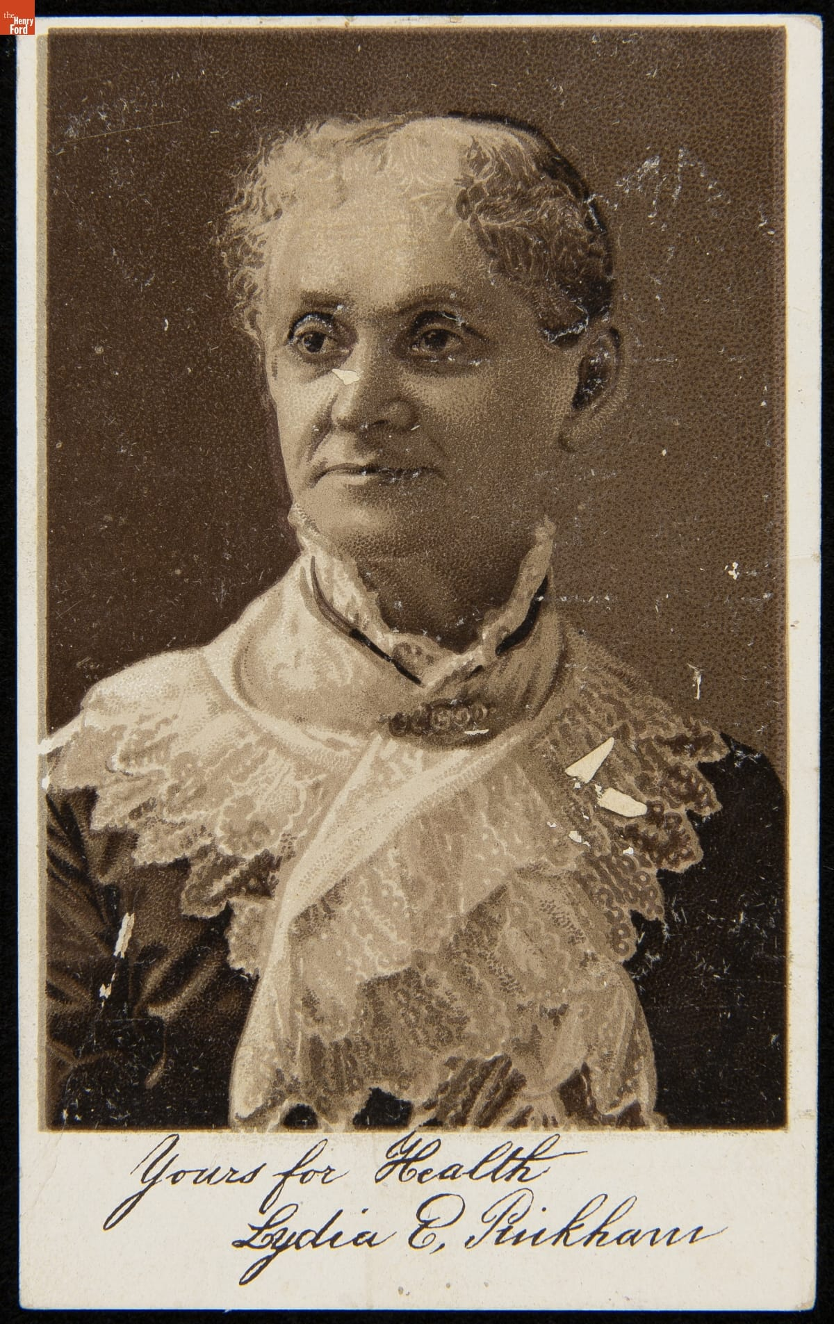 Torso and head of woman with elaborate lacy scarf pinned around her neck and chest; handwritten text