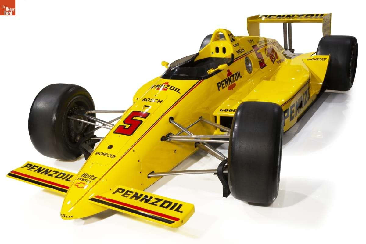 Low, bright yellow race car with large wideset tires and black and red text and decoration