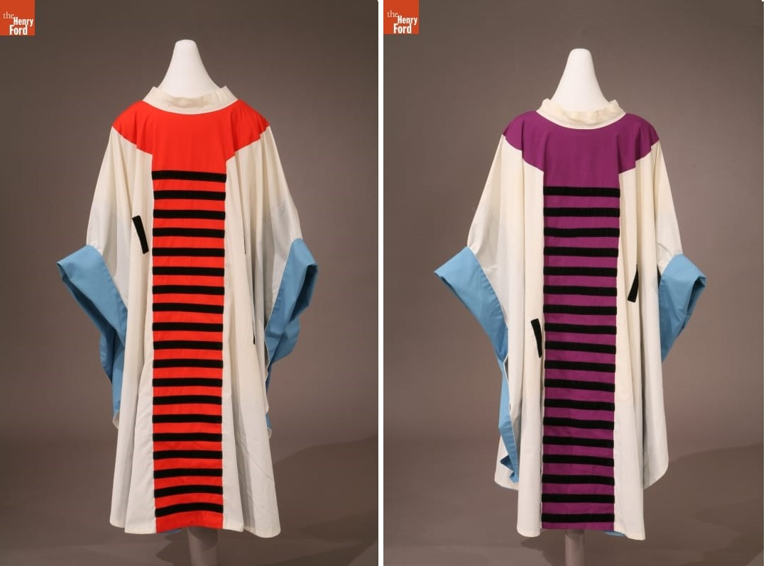 Two white robes with blue bands around the wrists, one with a red center panel with black stripes; the other with an purple center panel with black stripes