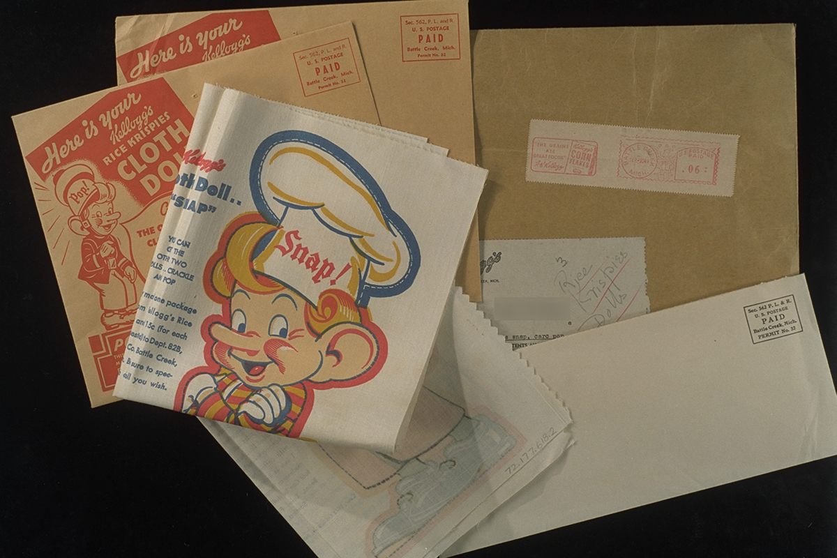 "Several mailing envelopes and folded fabric showing elf head and torso with ""Snap!"" printed on chef's hat"