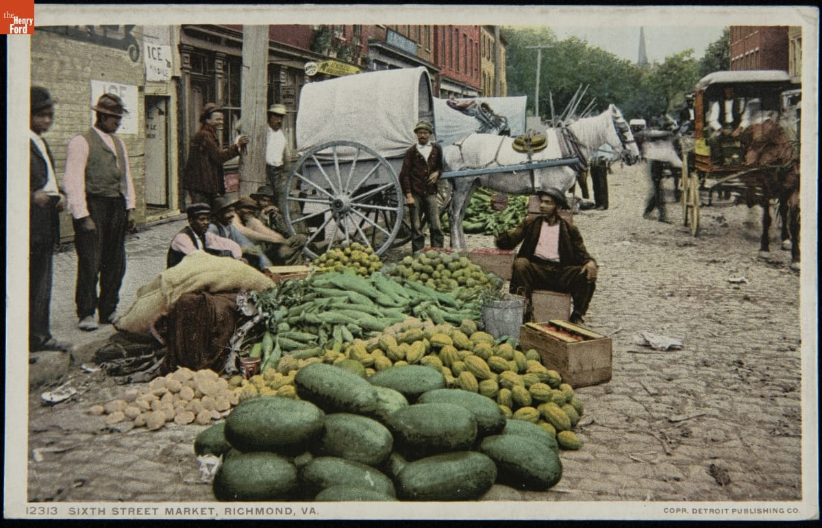 Men of color sit and stand around a piles of different vegetables at one side of a cobblestone street with buildings and horses and carriages behind them