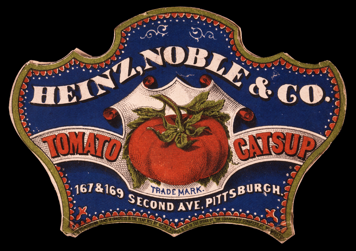 Fancy-shaped blue, gold, red, and white label with a picture of a tomato and text