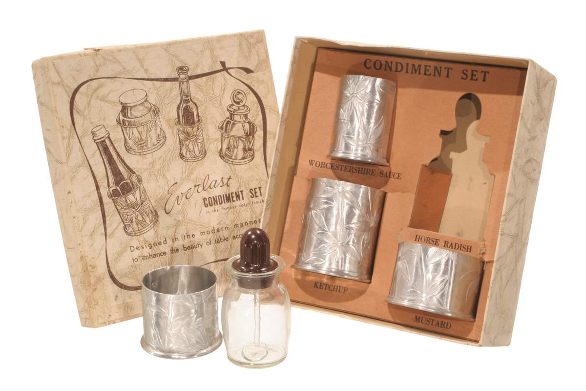 Box containing silver canisters; additional silver canister and glass in front; box lid with text and drawings of canisters nearby