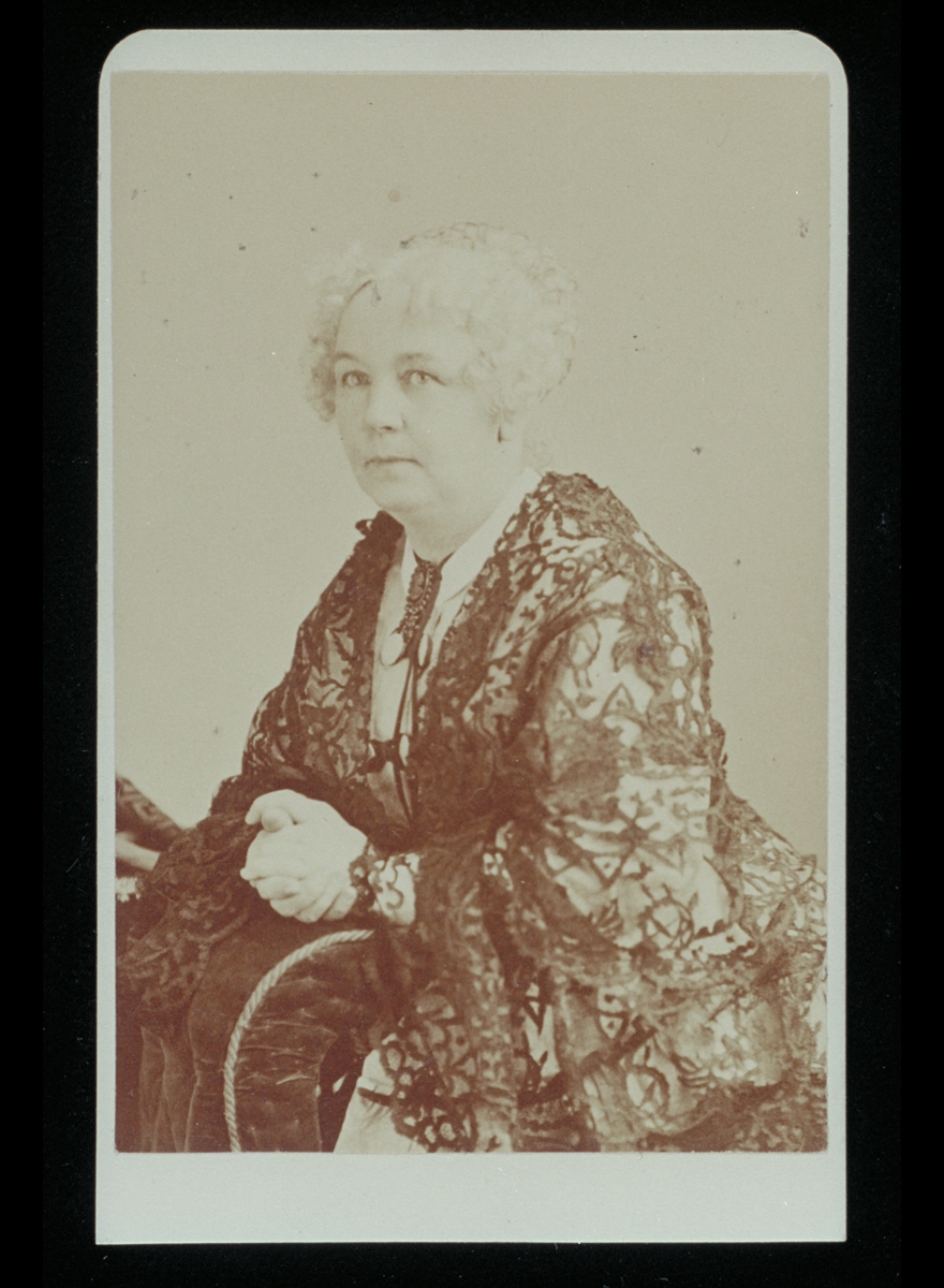Black-and-white portrait of woman with light-colored hair and clasped hands wearing elaborate lace dress.