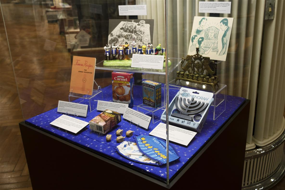 Display case with dark base and clear cover, containing various items on lucite display stands and cards with text on them