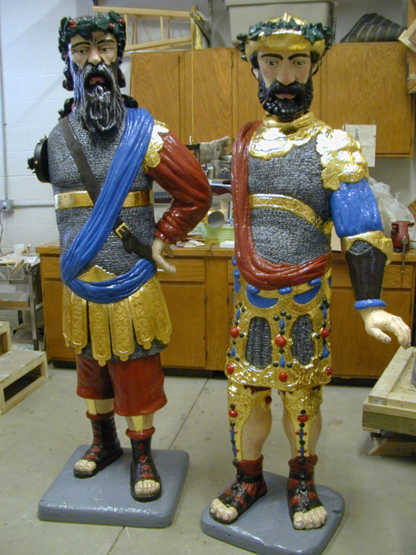 Two colorful sculptures of bearded men wearing elaborate costumes
