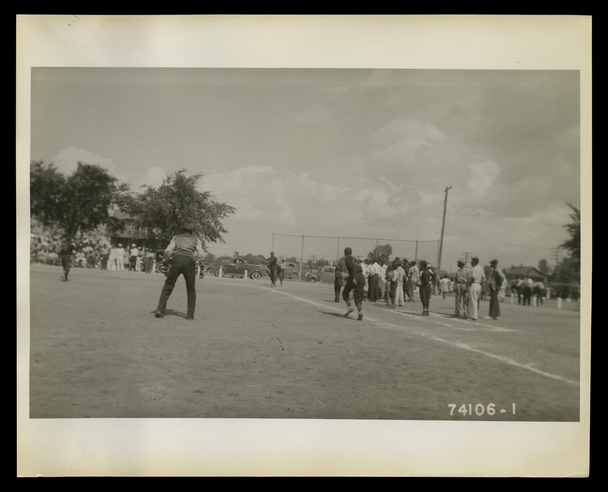 People, many or all African American, play baseball on a field while others look on