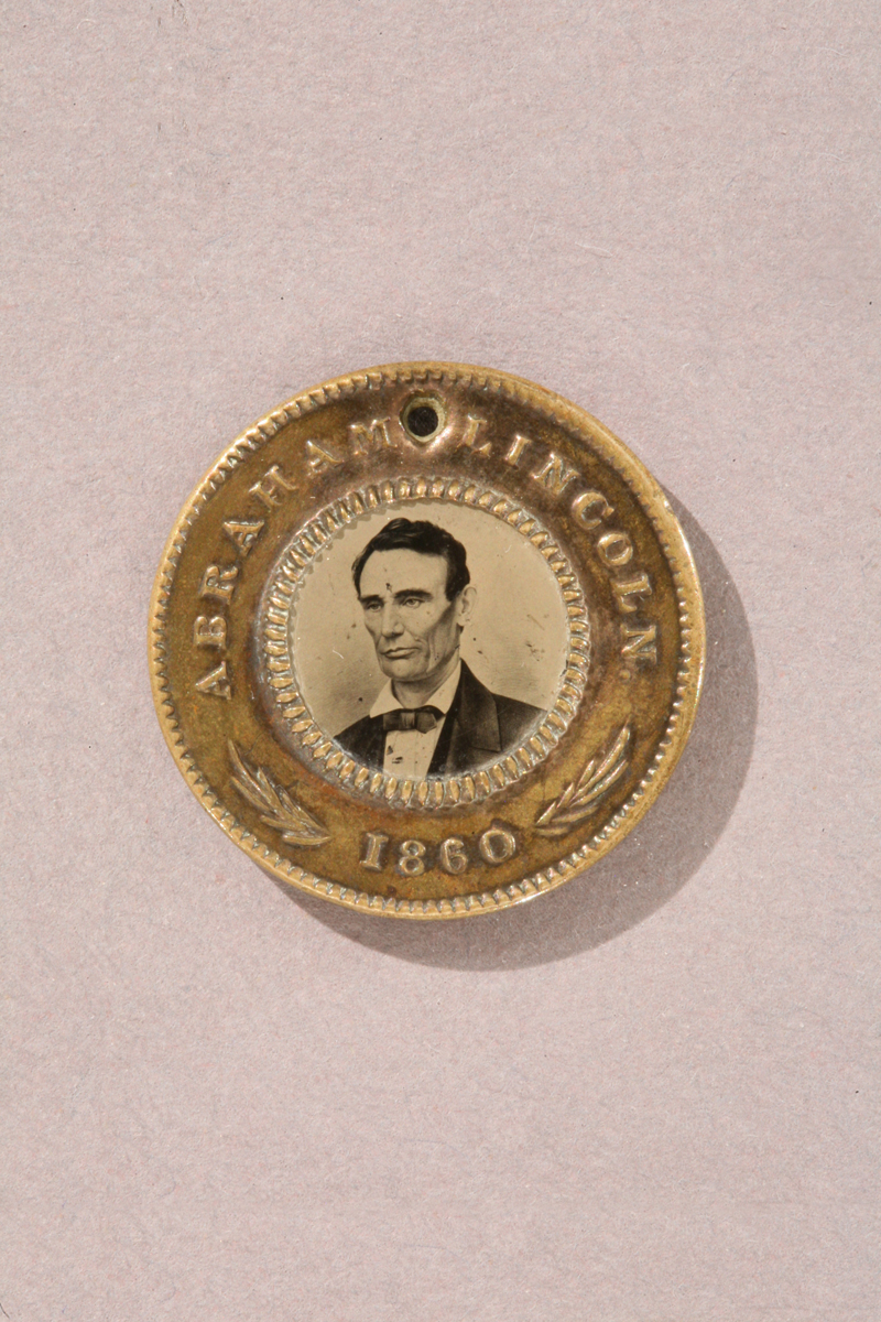 "Gold colored button with text ""Abraham Lincoln 1860"" and portrait of man in center"