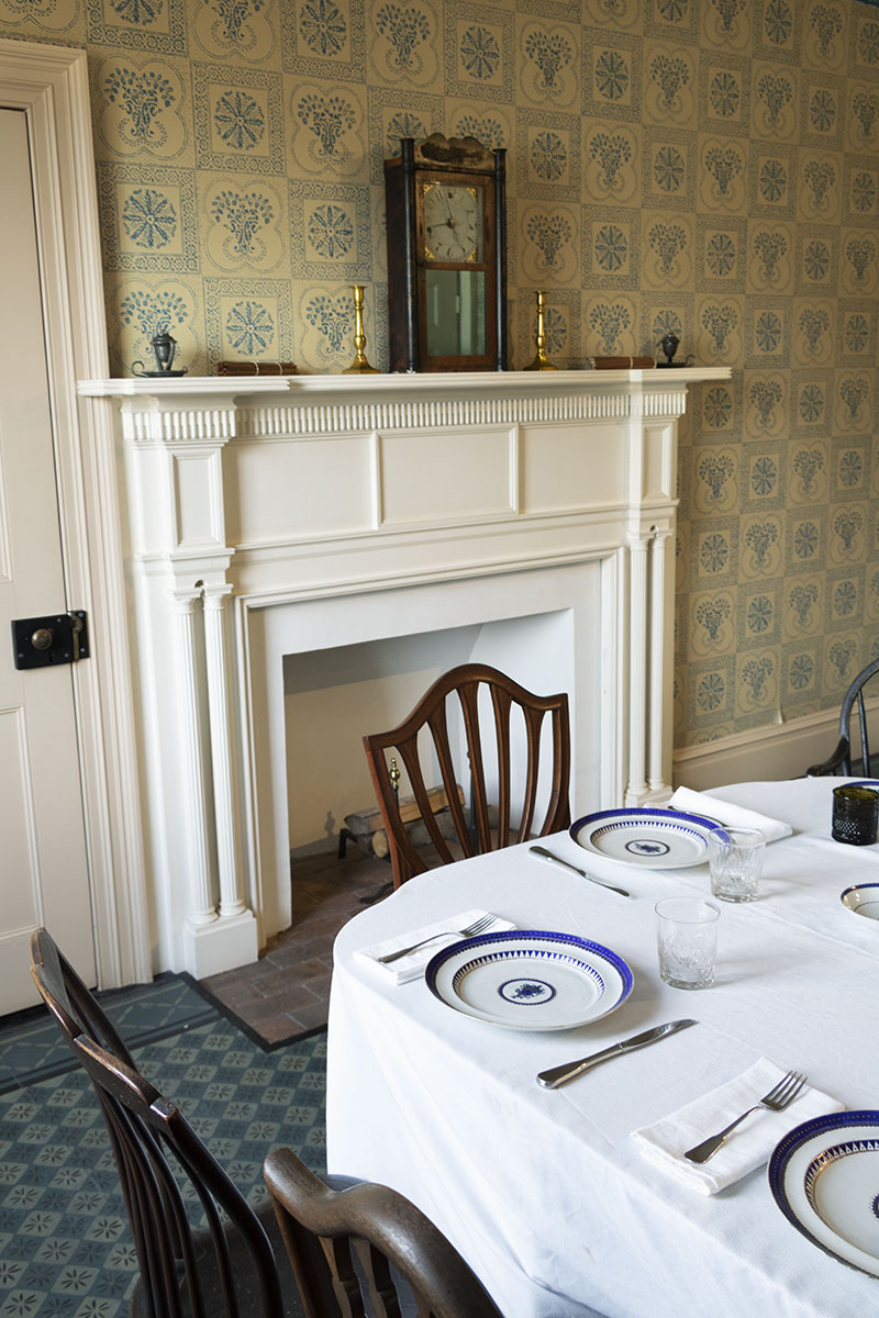 Corner of set table with chairs; fireplace with mantel behind and patterned wallpaper on walls