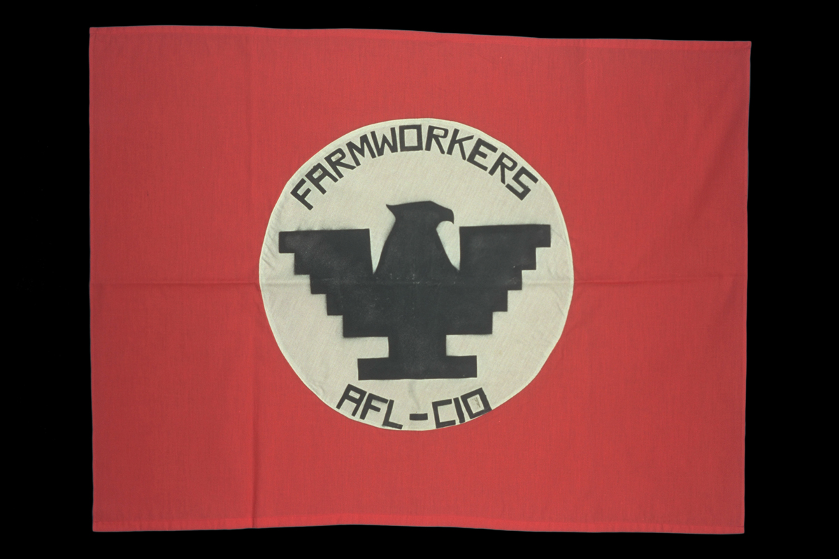 "Red flag with white circle in middle containing stylized black eagle and text ""FARMWORKERS AFL-CIO"""