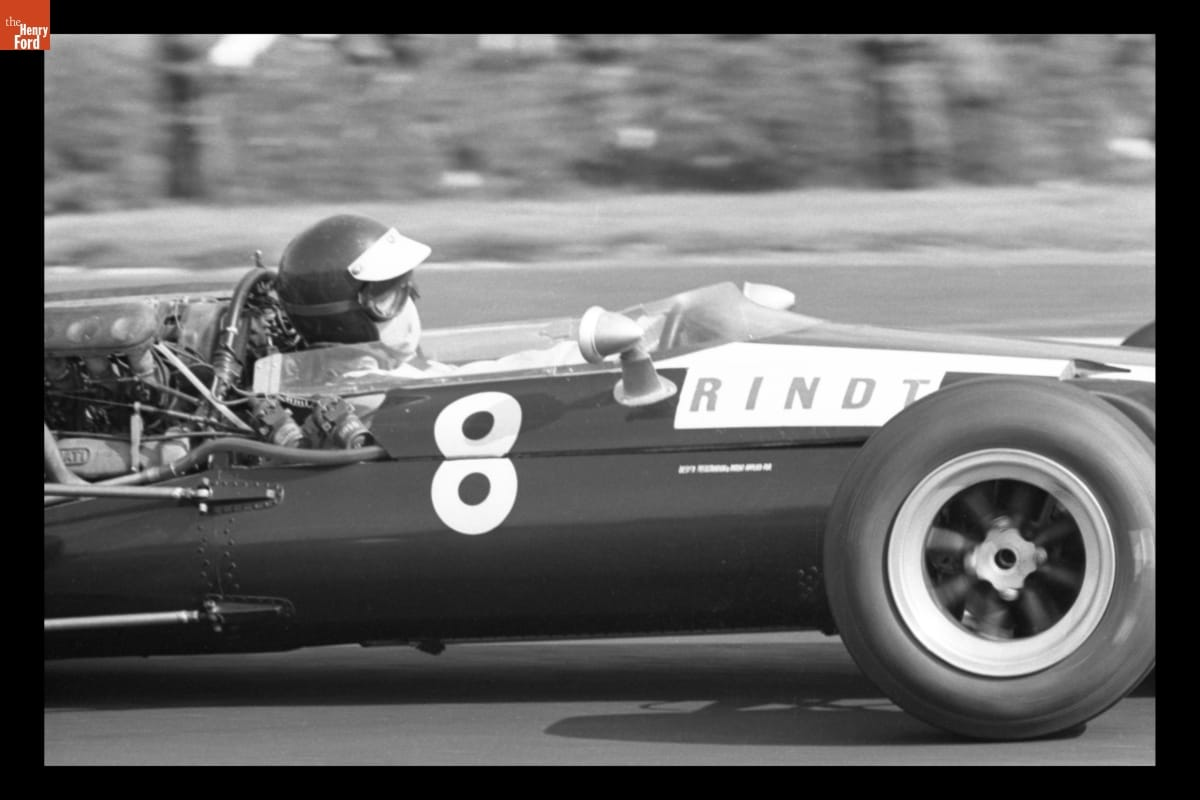 "Partial side view of racecar with text ""8"" and ""RINDT"" on side; person inside in helmet, goggles, and mouth covering"
