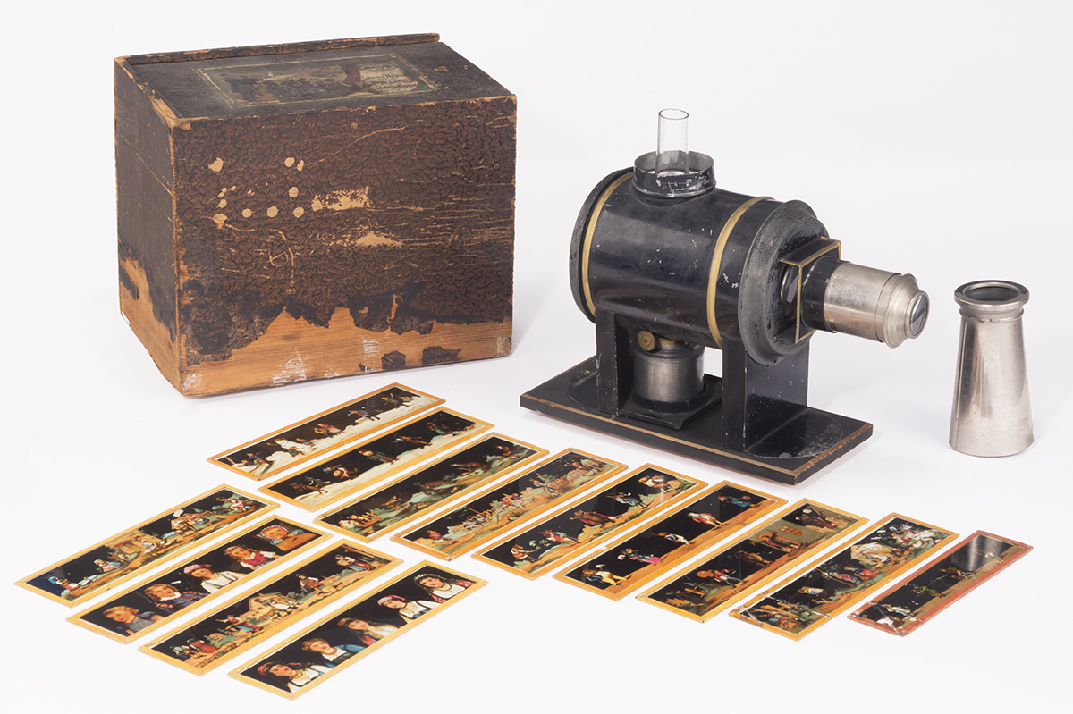 Wooden box, strips of translucent images, and small metal and glass machine