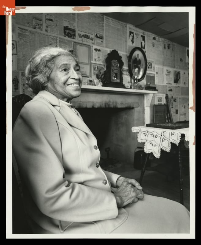 Woman with hair pulled back wearing suit jacket sits in chair with mantel and wall covered in newspaper behind her