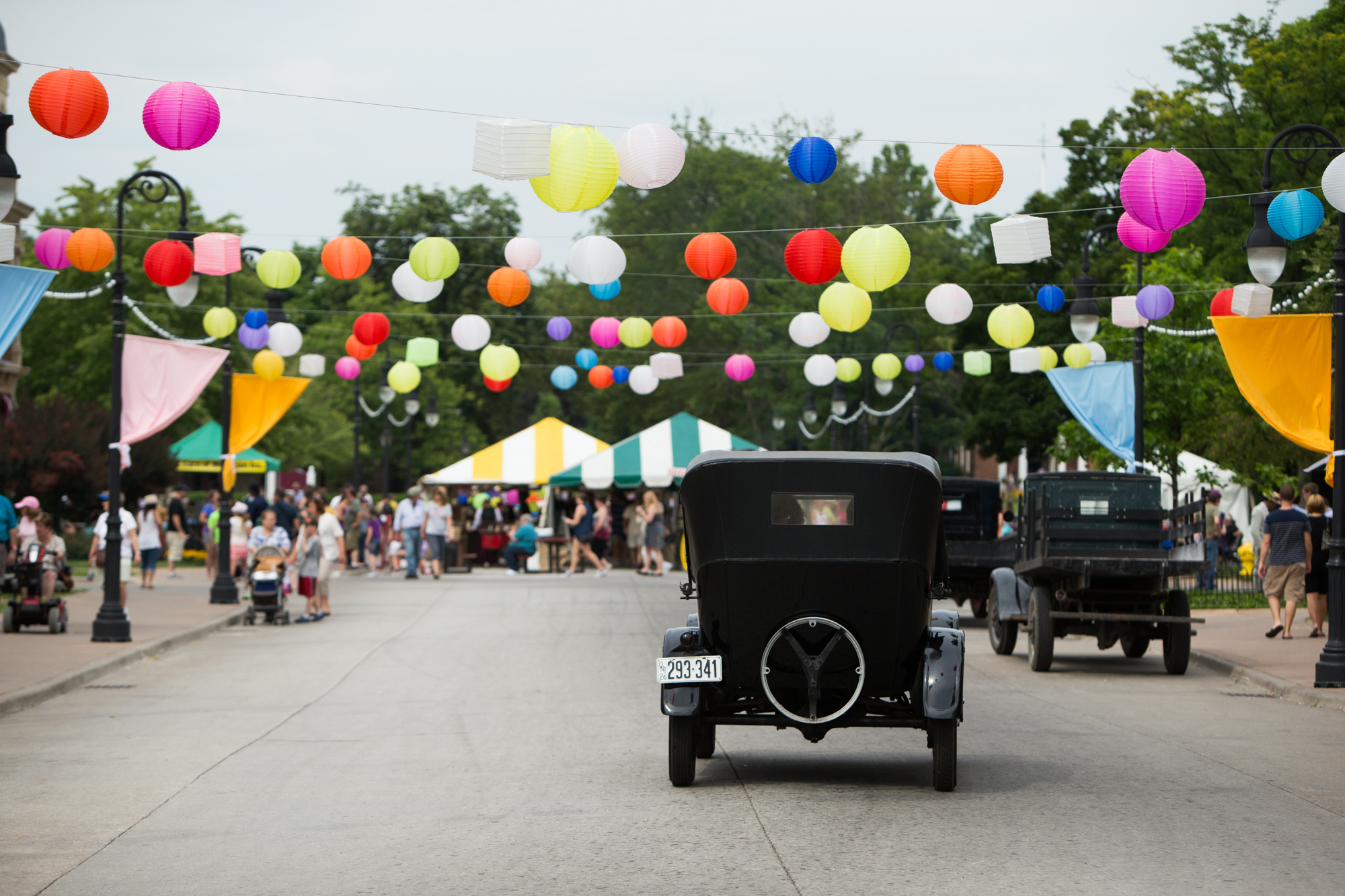 Antique car driving down a street festooned with balloons