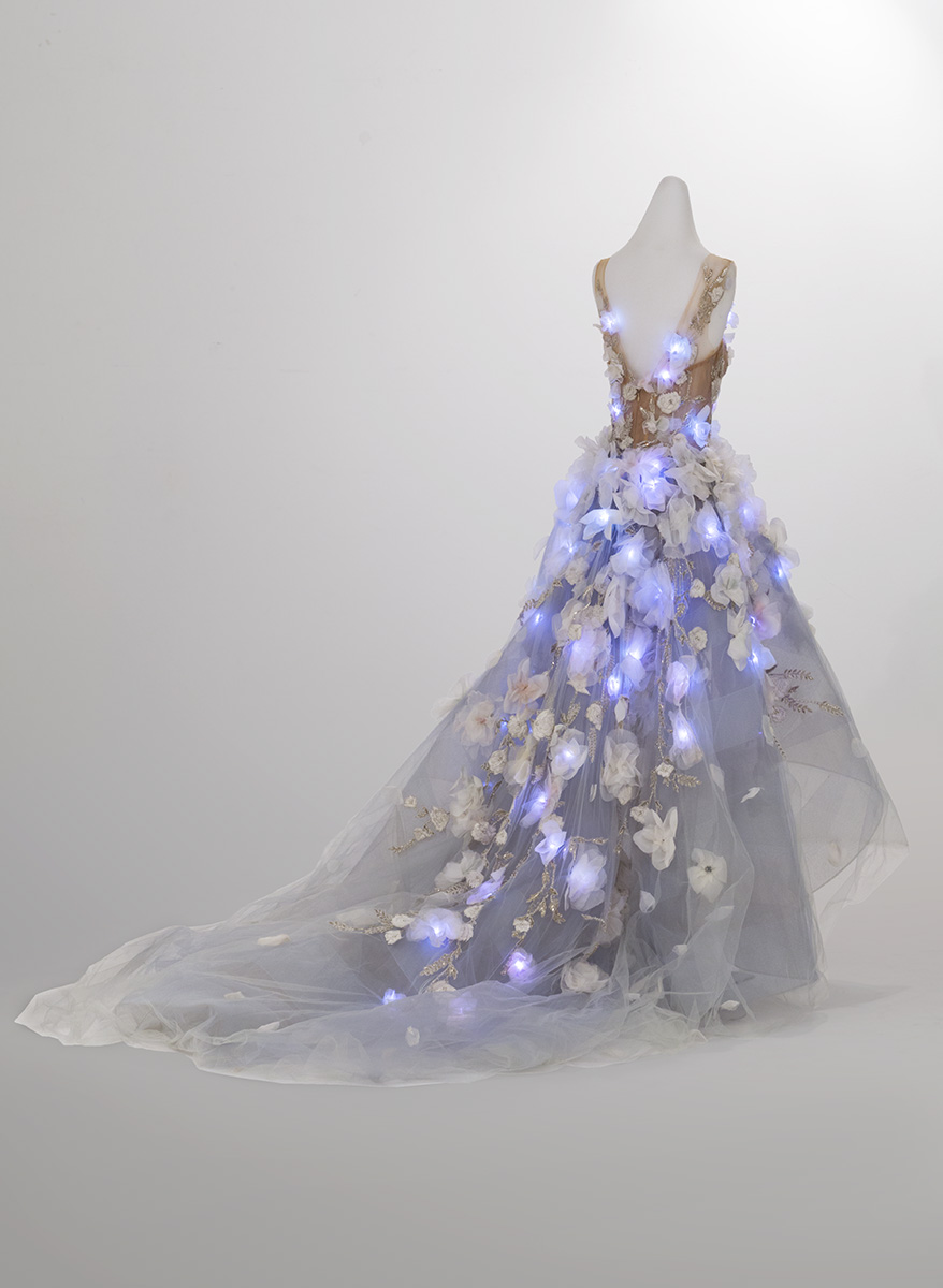 Back view of dress on dress form with glowing blue lights integrated into bodice and skirt