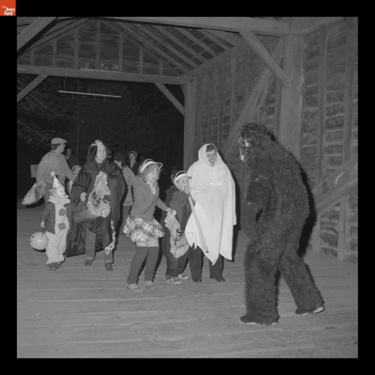 Person in a gorilla costume in front of adults and children, many in costume, in a wooden covered bridge