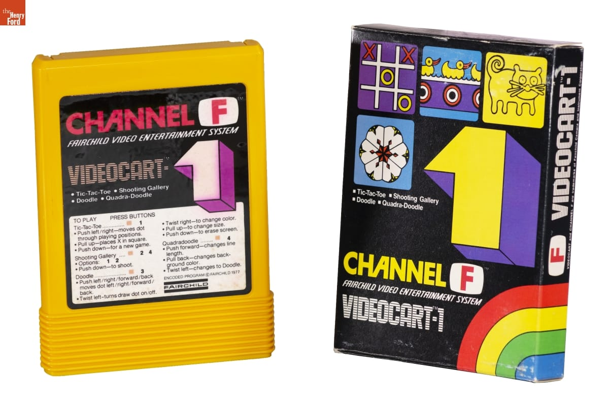 Boxy yellow game cartridge with graphic label containing text, next to black box with graphics and text