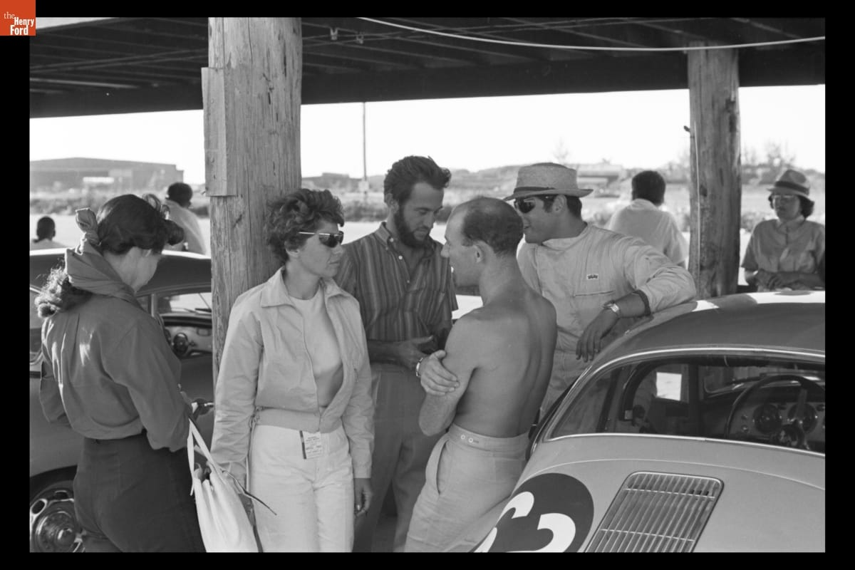 Woman leans against wooden post and talks to several other people, with additional people and cars nearby