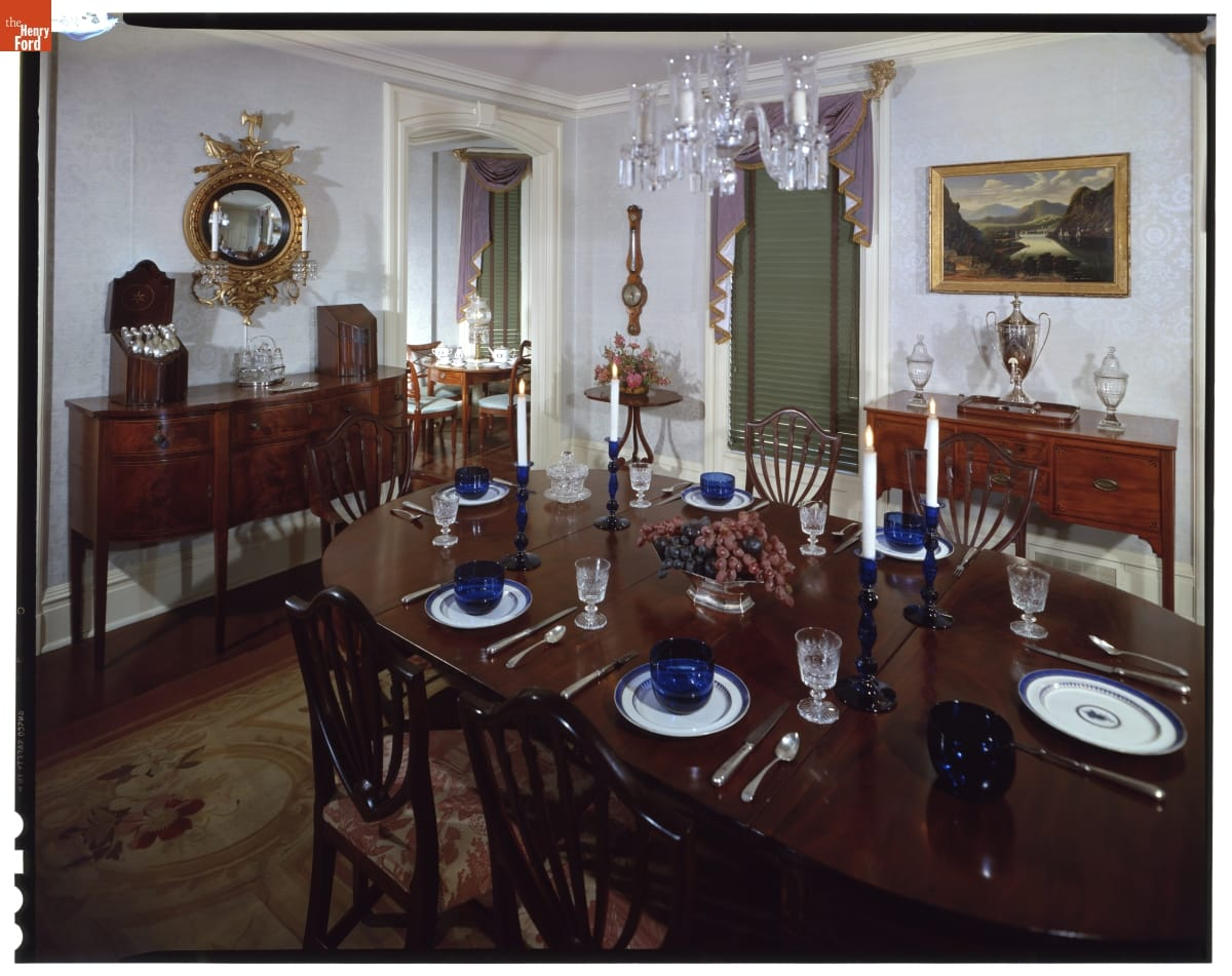 Dining room with elaborate furnishings, including set table and chairs and two sideboards