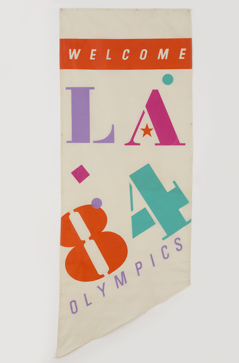 "White banner with colorful graphic characters ""L A 8 4"" and additional text ""WELCOME"" and ""OLYMPICS"""