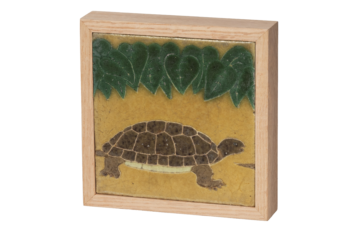 Tile of turtle on yellow background under green leaves