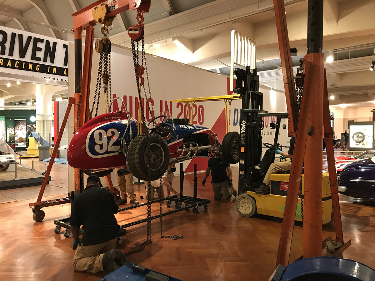 Red and blue race car suspended from a gantry and forklift with men kneeling by it
