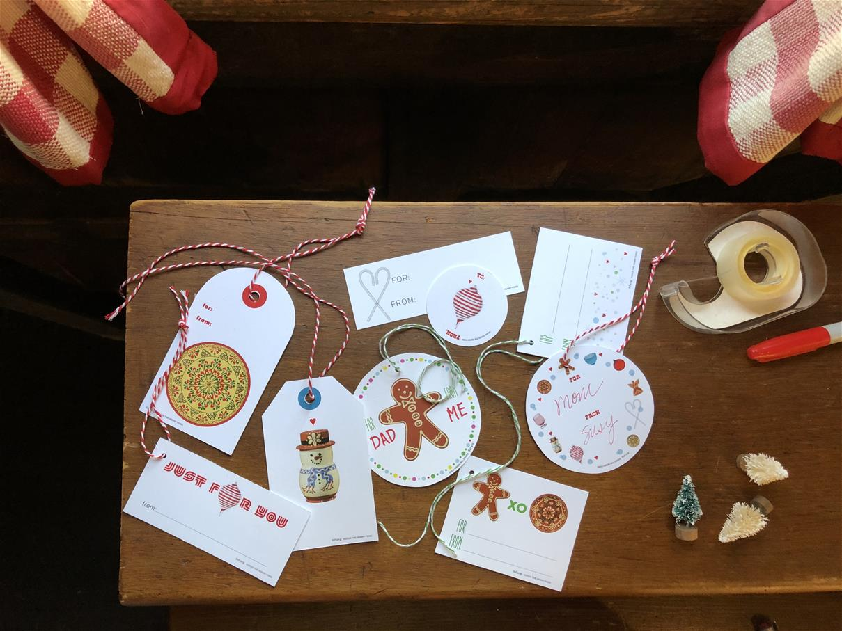 Various shapes and designs of holiday labels on a wood table with tape, scissors, and tiny Christmas trees