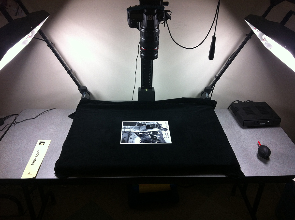 Photograph lying on black fabric with lights on either side and a camera pointed downward at it