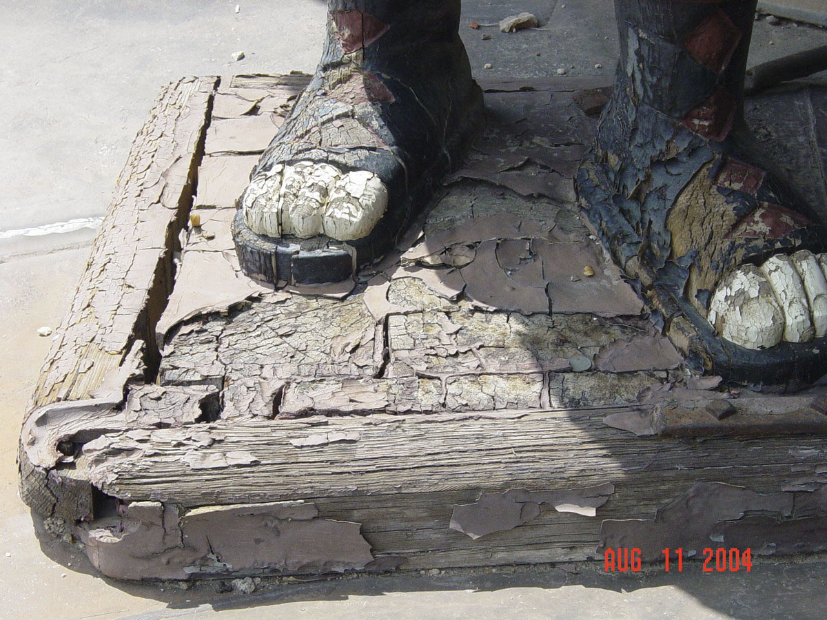 Statue base and sculpted feet of very cracked wood