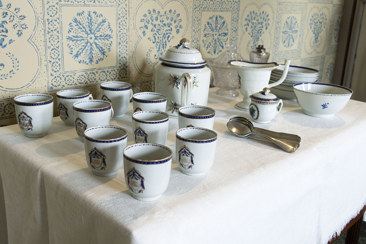 Table containing white dishes with blue pattern; wallpapered wall in background