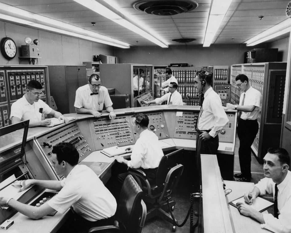 Group of men sitting and standing at computer consoles and banks