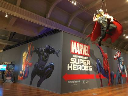 Gray wall with images and text in larger building; hanging figure of superhero in right foreground