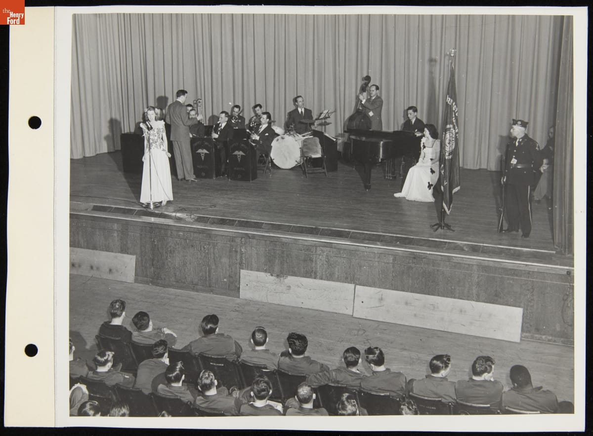Men with instruments and two women, one at a microphone, on a stage with a soldier in front of an audience