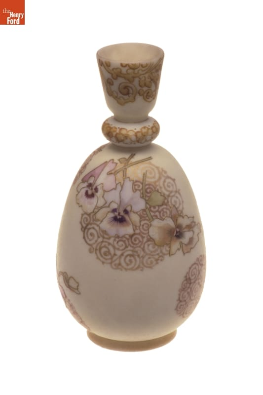 Beige vase with intricate top and pattern of pansies and swirls