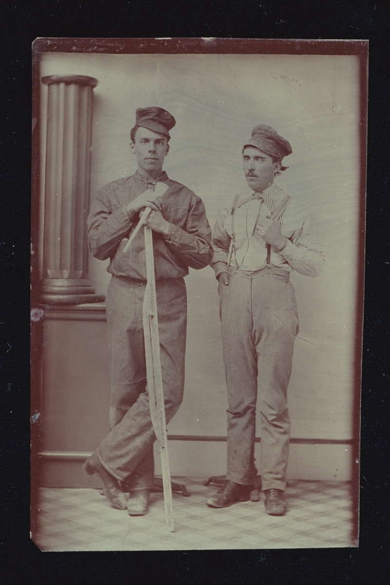 Two men in caps, one holding a long tool, standing next to a pillar