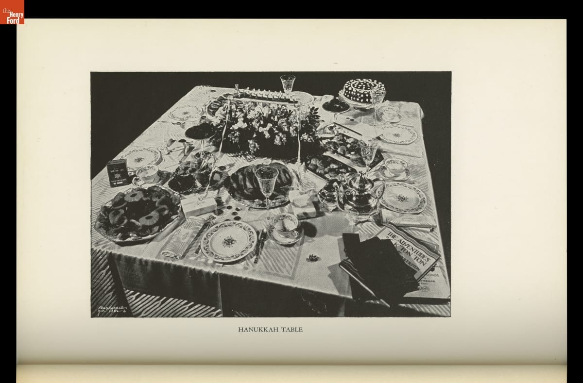"Image labeled ""Hanukkah Table"" of decorated table with place settings, food, books"
